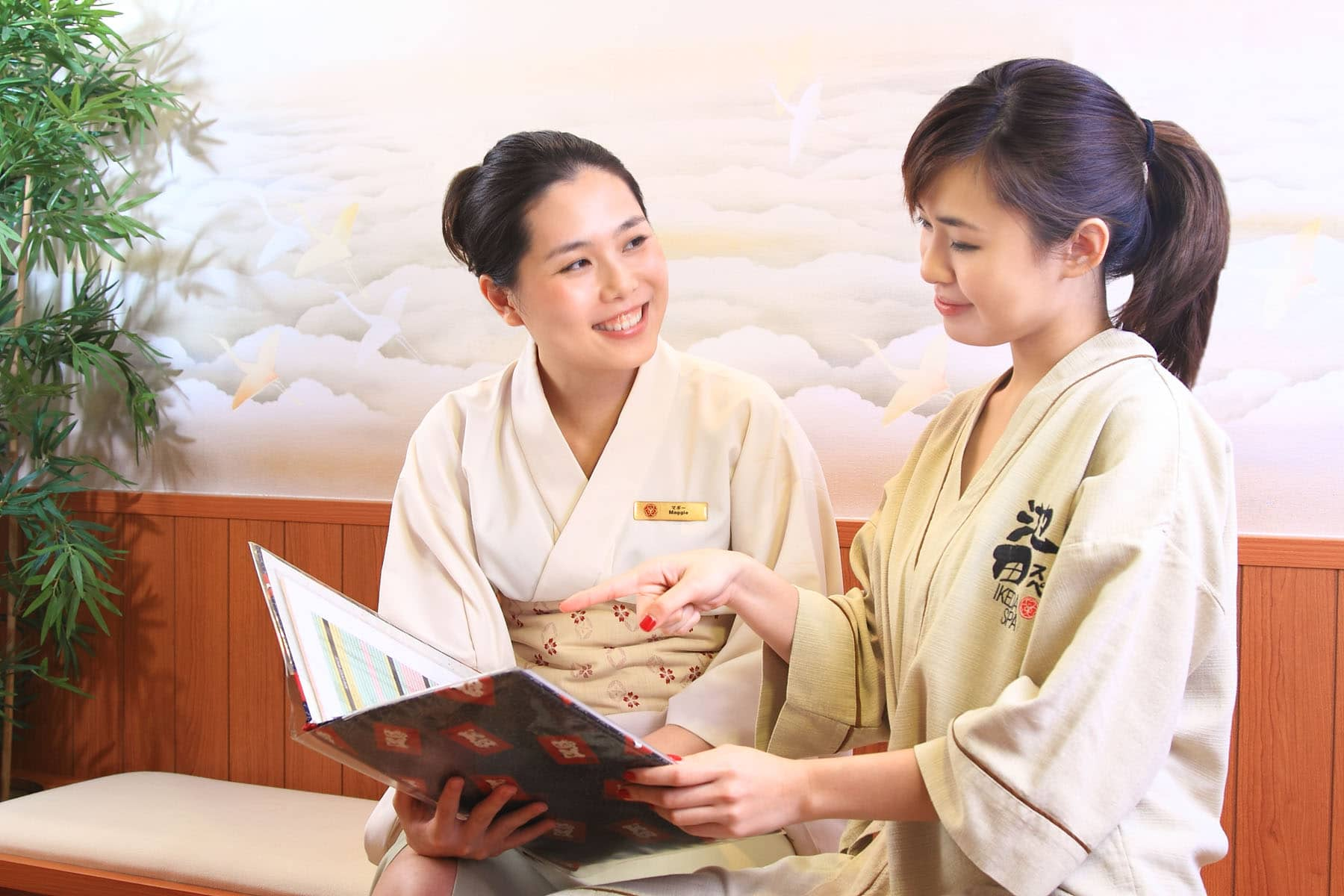 Ikeda Spa therapist showing the spa menu to customers