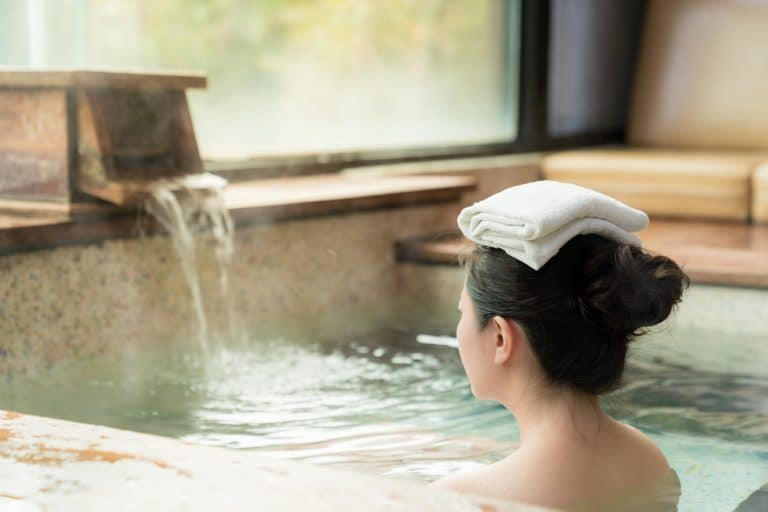 Towel on lady's head while she is taking an onsen